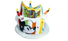 A hat shaped like a birthday cake with candles features Mickey Mouse and a colorful Happy Birthday message.