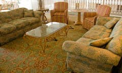 Finely upholstered living room with glass coffee table and area rug